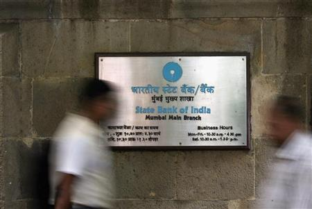 People walk in front of a signboard displayed at the head office of State Bank of India in Mumbai November 9, 2009. REUTERS/Arko Datta/Files