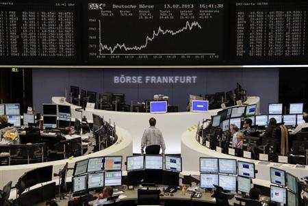 Traders are pictured at their desks in front of the DAX board at the Frankfurt stock exchange February 13, 2013. REUTERS/Remote/Janine Eggert