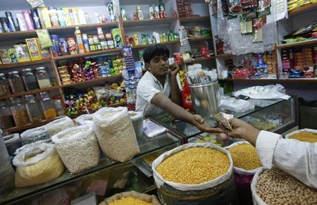 The owner of a 'Kirana' or mom-and-pop grocery store accepts money from a customer in his shop in Mumbai December 7, 2012. REUTERS/Vivek Prakash/Files