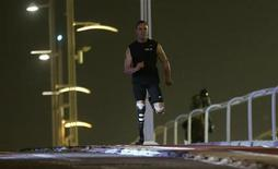 Le Sud-Africain Oscar Pistorius, premier double amputé à avoir participé à une course olympique parmi les valides, a été arrêté jeudi après le meurtre de sa compagne à son domicile. Selon la radio 702 de Johannesburg, l'athlète, qui l'aurait confondue avec un intrus, l' aurait touchée mortellement au bras et à la tête avec une arme à feu. /Photo d'archives/REUTERS/Fadi Al-Assaad