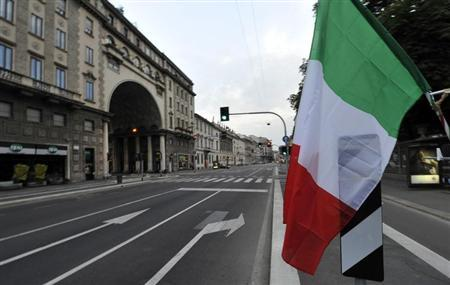 An Italian flag is seen on an empty street during the Euro 2012 final soccer match between Italy and Spain in downtown Milan July 1, 2012. REUTERS/ Paolo Bona