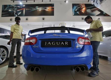 Showroom attendants polish a Jaguar vehicle at a Jaguar Land Rover showroom in Mumbai February 13, 2013. REUTERS/Vivek Prakash