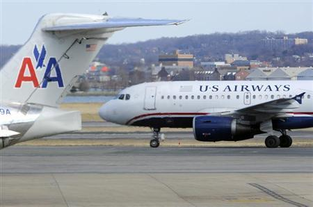 A US Airways plane (R) taxis for takeoff past an American Airlines plane at the Ronald Reagan Washington National Airport in Arlington County, Virginia, February 10, 2013, as negotiations continue this week between parent companies US Airways Group Inc and AMR Corp on a possible $11 billion merger, creating what would be the world's largest airline. REUTERS/Mike Theiler (UNITED STATES - Tags: TRANSPORT BUSINESS) - RTR3DLGO