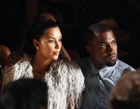 Kanye West drapes his arm over the shoulder of Kim Kardashian as they watch a showing of the Marchesa Spring/Summer 2013 collection during New York Fashion Week, September 12, 2012. REUTERS/Lucas Jackson