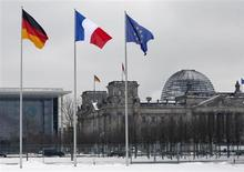 A German, French and an EU flag flutter over the German lower house of parliament in Berlin January 22, 2013. REUTERS/Fabrizio Bensch