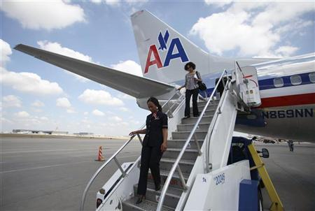 American Airlines flight attendant Karen Stewart walks down from the rear exit of an American Airlines Boeing 737 at DFW International Airport as officials of AMR, American Airlines, Boeing and Airbus announce a major airplane manufacturing deal during a news conference at the airport in Dallas, Texas July 20, 2011. REUTERS/Darrell Byers