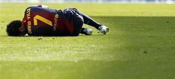 """Нападающий """"Барселоны"""" Давид Вилья лежит на газоне в матче против """"Хетафе"""" в Барселоне 10 февраля 2013 года. Нападающий каталонской """"Барселоны"""" Давид Вилья вернулся в больницу, так и не сумев избавиться от камней в почках, и теперь не сможет помочь своей команде в матче чемпионата Испании против """"Гранады"""", который пройдет в субботу, сообщил клуб на своем сайте (www.fcbarcelona.es). REUTERS/Albert Gea"""