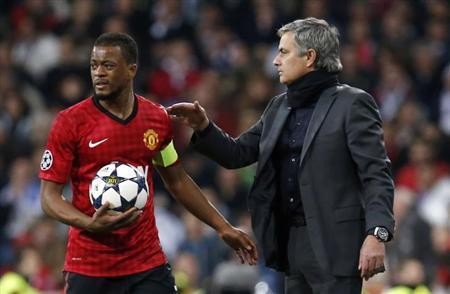 Real Madrid's coach Jose Mourinho (R) gives the ball to Manchester United's Patrice Evra during their Champions League soccer match at Santiago Bernabeu stadium in Madrid, February 13, 2013. REUTERS/Sergio Perez