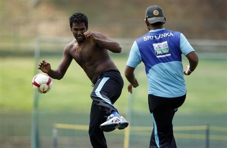Sri Lanka's Angelo Mathews (L) plays with a soccer ball during a practice session ahead of their third and final test cricket match against Pakistan in Pallekele July 7, 2012. REUTERS/Dinuka Liyanawatte/Files