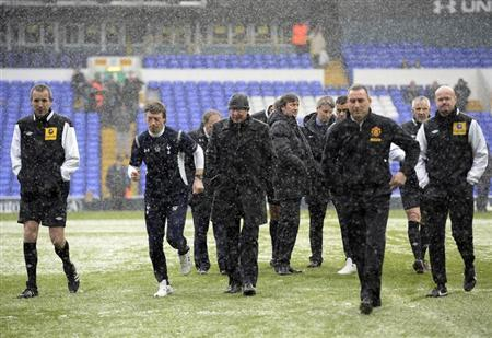 Match officials and Manchester United's manager Alex Ferguson (4th L) leave after inspecting the pitch, as snow falls, before the Premier League soccer match between Tottenham Hotspur and Manchester United at White Hart Lane in London January 20, 2013. REUTERS/Dylan Martinez