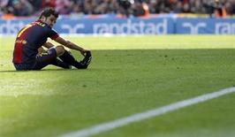 El delantero azulgrana David Villa ha regresado al hospital tras una recaída en su recuperación de un cólico nefrítico y se queda fuera del partido de Liga del sábado contra el Granada, dijeron el jueves los líderes de la clasificación. En la image, David Villa permanece sentado en el campo tras caer por una falta durante el partido de Liga contra el Getafe, en el Camp Nou, Barcelona, el 10 de febrero de 2013. REUTERS/Albert Gea