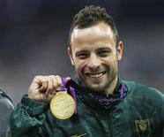 """Velocista sul-africano, Oscar Pistorius, comemora com medalha de ouro após vencer corrida durante os Jogos Paralímpicos, em Londres. Pistorius, ídolo olímpico e paralímpico conhecido como """"Blade Runner"""" devido às próteses que usa para correr, foi detido nesta quinta-feira após a morte da namorada dele a tiros em sua casa, em Pretória. 08/09/2012 REUTERS/Eddie Keogh"""