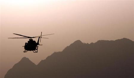A helicopter is seen silhouetted in Kandahar province, southern Afghanistan, March 20, 2009. REUTERS/Stefano Rellandini/Files