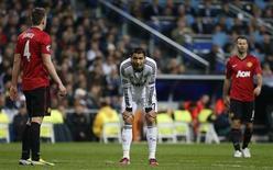 El empate 1-1 del Real Madrid el miércoles en casa contra el Manchester United deja equilibrado el enfrentamiento de octavos de final en la Liga de Campeones y el partido de vuelta del 5 de marzo llegará al final de una semana que podría hacer o deshacer la temporada del club merengue. En la imagen, Cristiano Ronaldo reacciona tras desaprovechar una oportunidad de gol durante el partido de Liga de Campeones contra el Manchester United en el Santiago Bernabéu, en Madrid, el 13 de febrero de 2013. REUTERS/Paul Hanna