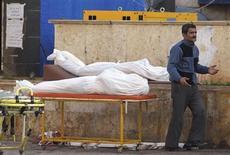 Homem passa perto de dois corpos, em frente a um hospital em Aleppo, na Síria. Pelo menos 100 soldados sírios e 30 rebeldes da milícia Frente Al Nusra, ligada à Al Qaeda, morreram em três dias de combates em uma cidade perto da fronteira iraquiana tomada pelos insurgentes na quinta-feira, informou um grupo de oposição que monitora o conflito sírio. 13/02/2013 REUTERS/Muzaffar Salman