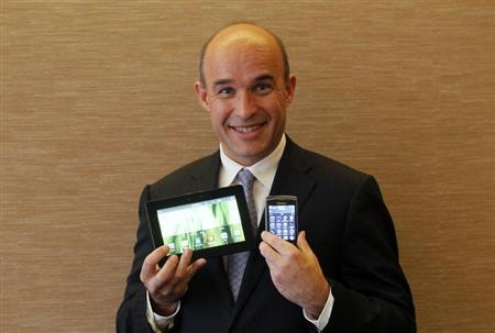 Research In Motion (RIM) Co-Chief Executive Jim Balsillie smiles as he poses with a PlayBook tablet computer (L) and a Blackberry Torch during an interview at the G20 CEO Summit in Seoul November 10, 2010. REUTERS/Aly Song
