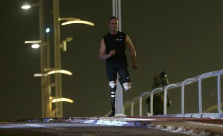 South Africa's Oscar Pistorius, an Olympics and Paralympics athlete, runs alongside a pure-bred Arabian race horse during the Doha GOALS (Gathering of all Leaders in Sport) forum at the Aspire Zone outdoor circuit in Doha December 12, 2012. REUTERS/Fadi Al-Assaad