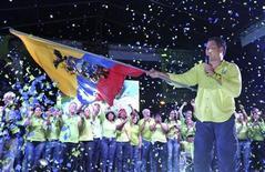 Presidente do Equador, Rafael Correa, flameja bandeira nacional durante comício em Guayaquil, Equador. Correa, um dos líderes de esquerda mais combativos da América Latina, deve ganhar facilmente a reeleição no domingo graças aos gastos pesados do Estado, que têm beneficiado os pobres. 13/02/2013 REUTERS/Gary Granja