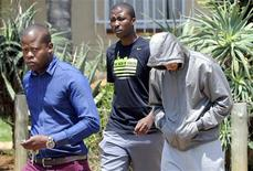 """South African """"Blade Runner"""" Oscar Pistorius (R) is escorted by police at a Pretoria police station February 14, 2013. Pistorius, a double amputee who became one of the biggest names in world athletics, was charged on Thursday with shooting dead his girlfriend, model Reeva Steenkamp, at his upscale home in Pretoria. REUTERS/Stringer"""