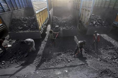 Labourers load coal onto trucks at a coal yard on the outskirts of Jammu March 23, 2012. REUTERS/Mukesh Gupta/Files