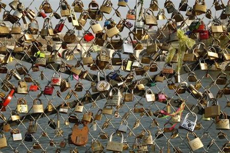 Some of the thousands of padlocks clipped by lovers onto the railings of the Pont des Arts bridge over the River Seine in Paris are seen March 16, 2012. REUTERS/Benoit Tessier