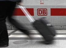 A traveller walks in front of a logo of German rail operator Deutsche Bahn at the Berlin Hauptbahnhof central station, October 6, 2009. REUTERS/Fabrizio Bensch