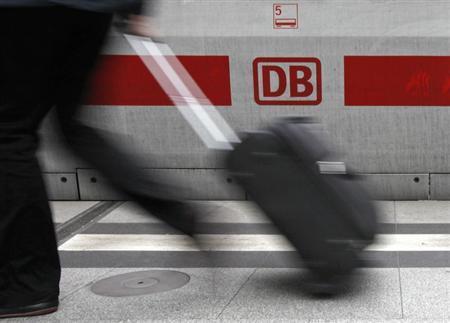 A traveller walks in front of a logo of German rail operator Deutsche Bahn at the Berlin Hauptbahnhof central station, October 6, 2009. REUTERS/Fabrizio Bensch