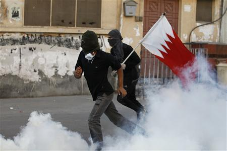 Anti-government protesters, one of them holding a Bahraini flag, run to take cover from tear gas fired by riot police to disperse them during clashes in the village of Sanabis, west of Manama February 14, 2013. REUTERS/Hamad I Mohammed
