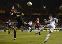 Gareth Bale (à droite) de Tottenham Hotspur et Anthony Réveillère de l'Olympique Lyonnais sur la pelouse de White Hart Lane, à Londres. Lyon a mordu la poussière jeudi face à Tottenham, victime du phénomène Gareth Bale, qui a inscrit le but de la victoire dans le temps additionnel (2-1). En marquant à l'extérieur, les joueurs de Rémi Garde conservent cependant un espoir de qualification. /Photo prise le 14 février 2013/REUTERS/Dylan Martinez