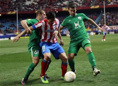 Atletico Madrid's Cristian Rodriguez (C) fights for the ball with Rubin Kazan's Gokdeniz Karadeniz (L) and Pablo Orbaiz during their Europa League soccer match at Vicente Calderon stadium in Madrid February 14, 2013. REUTERS/Susana Vera