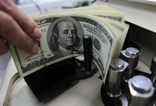 Bancária conta notas de dólar norte-americano em Bangcoc, na Tailândia. 12/10/2010 REUTERS/Sukree Sukplang