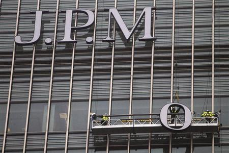 Workers erect a sign for JPMorgan investment bank at Canary Wharf in London December 21, 2011. EUTERS/Finbarr O'Reilly