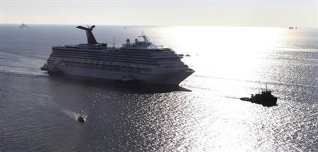 The Carnival Triumph cruise ship is towed towards the port of Mobile, Alabama, February 14, 2013. REUTERS/ Lyle Ratliff