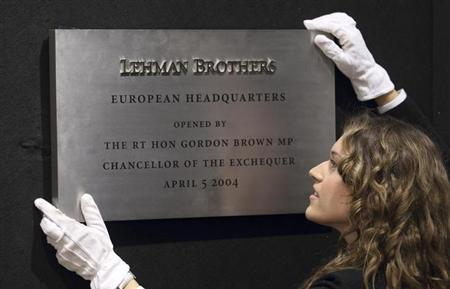 A Christie's employee poses for a photograph with the plaque from Lehman Brothers' European headquarters at Christie's in central London, September 24, 2010. REUTERS/Andrew Winning/Files