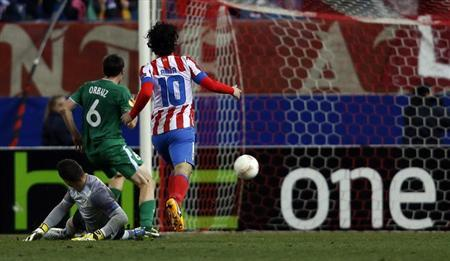 Atletico Madrid's Arda Turan (R) and goalkeeper Sergio Asenjo (bottom) watch as Rubin Kazan's Pablo Orbaiz scores during their Europa League soccer match in Madrid February 14, 2013. REUTERS/Susana Vera