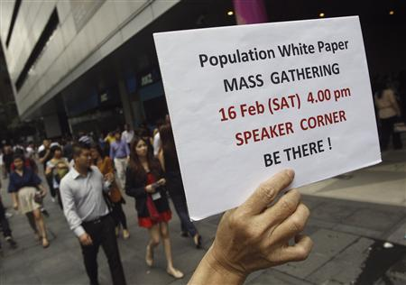 Eric Lim, a supporter of Saturday's public protest, holds up a poster to inform the public of the event, during lunch hour in the central business district Raffles Place in Singapore February 15, 2013. REUTERS/Edgar Su