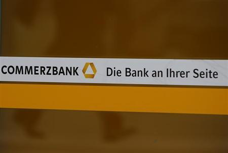 A person is reflected in a window of a branch of Germany's Commerzbank in Frankfurt February 12, 2013. The words read:''Commerzbank The bank at your side''. REUTERS/Lisi Niesner (GERMANY - Tags: BUSINESS)