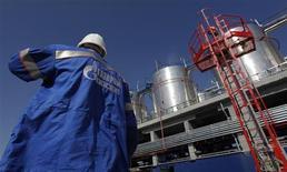 Рабочий стоит около оборудования на заводе Газпром-нефть в Москве, 20 сентября 2012 года. Цены на нефть снижаются после выхода слабых экономических данных еврозоны. REUTERS/Maxim Shemetov