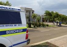 El sudafricano Oscar Pistorius, un doble amputado que se convirtió en uno de los grandes nombres del atletismo, va a comparecer el viernes ante un tribunal acusado de matar a su novia. En la imagen, un vehículo policial aparcado junto a la casa de Pistorius en Pretoria, el 14 de febrero de 2013. REUTERS/Andrea Ettwein
