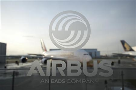 An A380 aircraft is seen through a window with an Airbus logo during the EADS / Airbus 'New Year Press Conference' in Hamburg January 17, 2012. REUTERS/Morris Mac Matzen