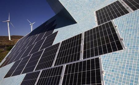The solar panels of a bioclimatic house are seen next to windmills on the grounds of the Technological and Renewable Energies Institute (ITER) outside Santa Cruz de Tenerife, in the Spanish Canary Island of Tenerife March 29, 2011. REUTERS/Santiago Ferrero