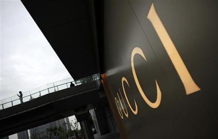 A man stands near a Gucci luxury boutique at the IFC Mall in Shanghai June 4, 2012. REUTERS/Carlos Barria