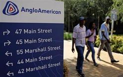 Люди проходят мимо стенда с логотипом Anglo American в Йоханнесбурге, 8 января 2013 года. Горнорудная компания Anglo American резко снизила прибыль в 2012 году из-за слабых результатов всех подразделений и сокращения стоимости платиновых активов и крупного железорудного проекта Minas Rio в Бразилии. REUTERS/Siphiwe Sibeko
