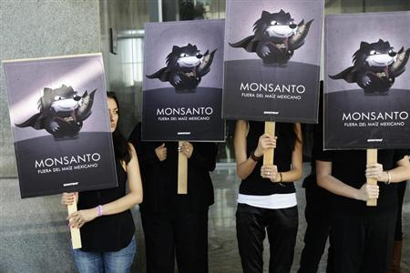 Greenpeace activists hold placards during a demonstration at Monsanto company offices in Mexico City October 16, 2012. REUTERS/Tomas Bravo
