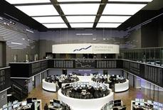 Traders are pictured at their desks in front of the DAX board at the Frankfurt stock exchange February 14, 2013. The euro tumbled to a three-week low against the dollar and plunged against the yen on Thursday after data painted a dismal picture of the euro zone's economy, raising the chances of European Central Bank monetary policy action. REUTERS/Pawel Kopczynski (GERMANY - Tags: BUSINESS)
