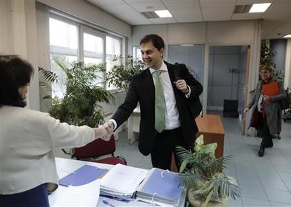 Greece's Secretary General for Public Revenue Harry Theoharis (C) shakes hands with an employee of Pallini's tax office during his visit in Pallini suburb, east of Athens February 15, 2013. REUTERS/John Kolesidis