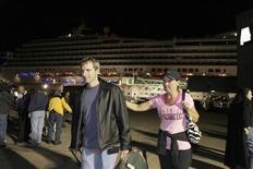 Passengers leave the Carnival Triumph cruise ship after reaching the port of Mobile, Alabama, February 14, 2013. REUTERS/Lyle Ratliff