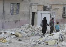 A family walk through rubble in the Al-Massir area in Aleppo February 13, 2013. REUTERS/Muzaffar Salman
