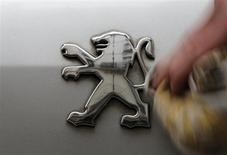 A man cleans a company logo on a Peugeot car parked in Paris, February 12, 2013. REUTERS/Christian Hartmann
