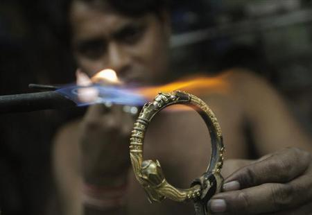 A goldsmith works on a gold bangle at a workshop in Kolkata January 16, 2013. REUTERS/Rupak De Chowdhuri/Files